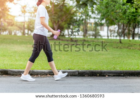 Woman walking in the park with bottle water in summer health care concept. Royalty-Free Stock Photo #1360680593