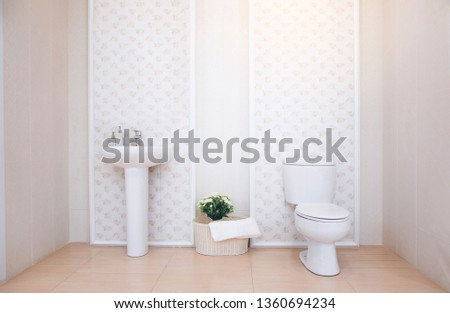 View of a spacious and elegant bathroom. Modern spacious bathroom with bright tiles with toilet and sink.  #1360694234