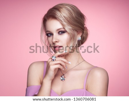 Portrait Beautiful Blonde Woman with Jewelry. Model Girl with Pearl Manicure on Nails. Elegant Hairstyle. Precious Stones and Silver. Beauty and Fashion Accessories. Perfect Make-Up. Pink Background #1360706081