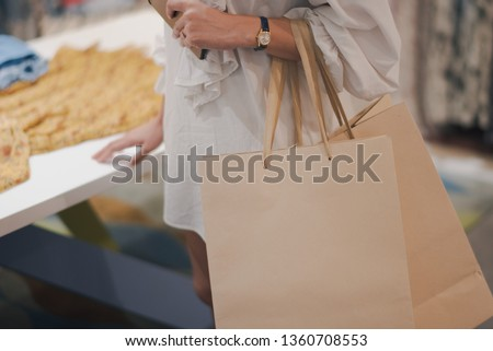 Closed up young woman shopping clothing in a shopping mall. Woman standing and holding a shopping bag in the store. #1360708553
