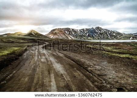 Beautiful Landmanalaugar gravel dust road way on highland of Iceland, Europe. Muddy tough terrain for extreme 4WD 4x4 vehicle. Landmanalaugar landscape is famous for nature trekking and hiking. Royalty-Free Stock Photo #1360762475