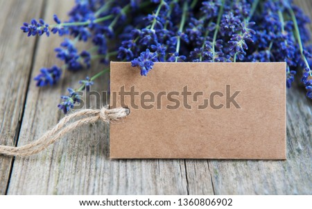 Empty tag and lavender flowers on a old wooden table #1360806902