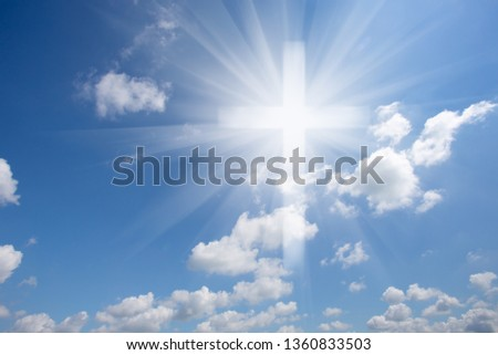 Christian shining cross in the blue cloudy sky. Symbol of faith and paradise. Conceptual collage.