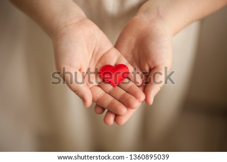 child hands holding red heart, health care, love and family concept, world heart day #1360895039