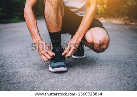 Runners tied in shoes,Man run on the street be running for exercise,Run sports background and closeup at running  shoe #1360928864