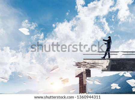 Businessman walking blindfolded on concrete bridge with huge gap as symbol of hidden threats and risks. Skyscape and nature view on background. 3D rendering. #1360944311