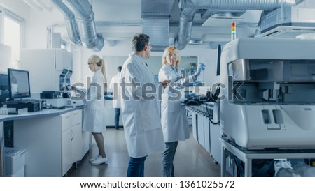 Team of Research Scientists Working On Computer, with Medical Equipment, Analyzing Blood and Genetic Material Samples with Special Machines in the Modern Laboratory. #1361025572
