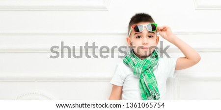 Fashion beautiful little boy in bright pants and t-shirt and scarf and sunglasses over white background,. Fashionable children #1361065754