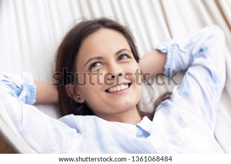 Young happy healthy woman relaxing on hammock dreaming resting in summer on vacation holiday, smiling carefree calm teen girl looking away chilling swinging lounging on peaceful warm spring day