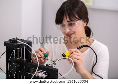 Young Female Technician Wearing Safety Eyeglasses Using Soldering Iron #1361083304