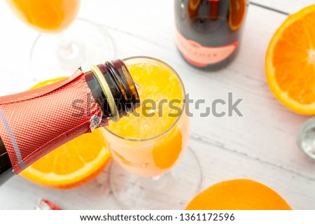 Lush mix drinks, summer alcoholic beverages and refreshing brunch mimosa cocktail concept with top view of orange fruits and champagne pouring from bottle of bubbly isolated on wooden table background #1361172596