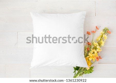 Blank white square pillow on white wood background with flowers, spring mock up