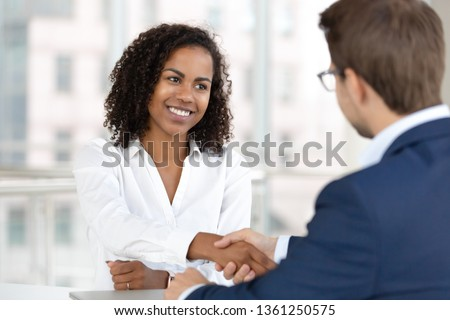 Smiling african female hr manager handshake hire male candidate at job interview make good first impression, happy mixed race client shake hand of bank broker, respect, business agreement concept Royalty-Free Stock Photo #1361250575
