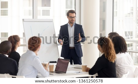 Male business coach speaker in suit give flipchart presentation, speaker presenter consulting training persuading employees client group, mentor leader explain graph strategy at team meeting workshop #1361250578
