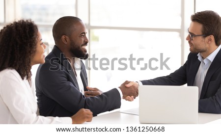 Happy african american couple shake hand of insurer salesman buy insurance services, black family clients customers handshake caucasian realtor broker make sale purchase deal agreement take bank loan #1361250668