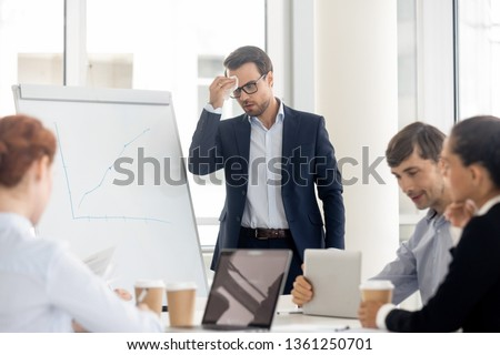 Nervous sweaty public speaker sweating wiping sweat afraid or speaking at presentation, stressed worried businessman presenter feel fear panic attack anxious about speech in front of business people #1361250701