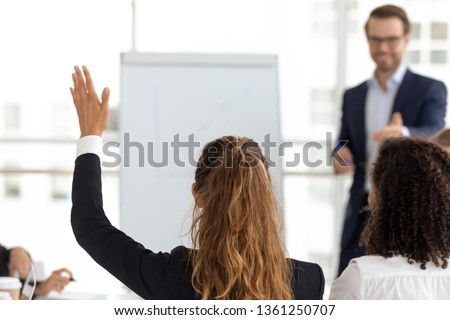 Training participant raise hand ask question get engaged involved in voting initiative at employees team workshop, corporate knowledge, business education, volunteer participation concept, rear view Royalty-Free Stock Photo #1361250707