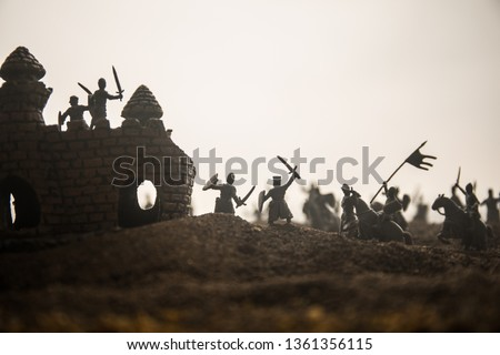 Medieval battle scene with cavalry and infantry. Silhouettes of figures as separate objects, fight between warriors on sunset foggy background. Selective focus #1361356115