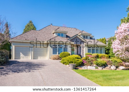 Beautiful exterior of newly built luxury home. Yard with green grass and walkway lead to ornately designed covered porch and front entrance. #1361417264