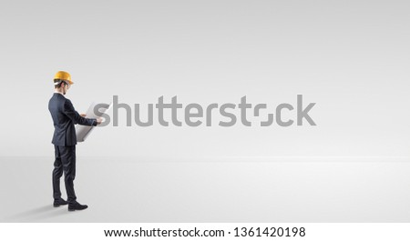 Young architect with construction helmet standing in an empty space and holding a plan #1361420198