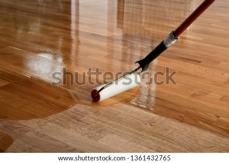 Lacquering wood floors. Worker uses a roller to coating floors. Varnishing lacquering parquet floor by paint roller - second layer. Home renovation parquet #1361432765