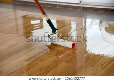 Lacquering wood floors. Worker uses a roller to coating floors. Varnishing lacquering parquet floor by paint roller - second layer. Home renovation parquet #1361432777