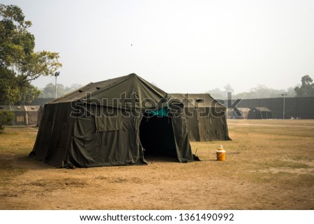 Military tent in the field. big tent city. field camp in nature. military base with temporary barracks. military exercises of the soldiers. large military tent. Army camp. reconstruction warfare #1361490992