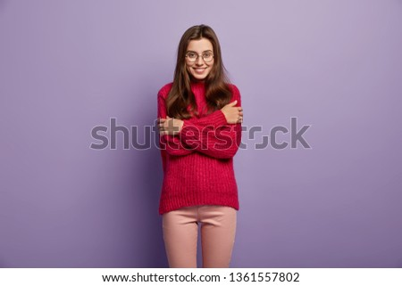 Indoor shot of pleased European woman crosses hands over chest, warms herself in winter red jumper, wears optical glasses, isolated over purple background. People, emotions and comfort concept #1361557802