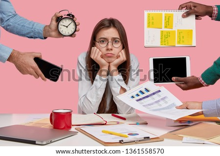 Sad female workaholic keeps hands under chin, busy making project work, studies papers, wears elegant white shirt, sits at desktop, unknown people stretch hands with notes, alarm clock, smartphone #1361558570