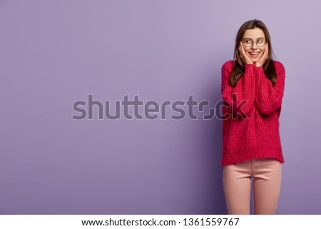 Half length shot of happy female puts both hands on face, smiles positively, wears long sleeved red jumper, looks right at copy space, isolated over purple background. Positive emotions concept #1361559767
