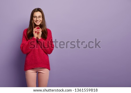 Happy Caucasian woman keeps hands in intriguing gesture, has positive look, pleasant smile, dressed in red knitted jumper, trousers, wears transparent glasses, isolated over lilac studio wall #1361559818