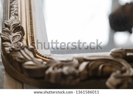 young girl restores the frame for the mirror. Female artisan hands working on a big wooden picture frame. Close up