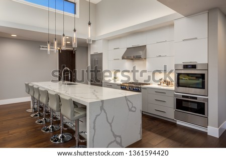 Beautiful Modern Kitchen In New Luxury Home. Features Large Waterfall Island with Double Ovens and Hardwood Floors #1361594420