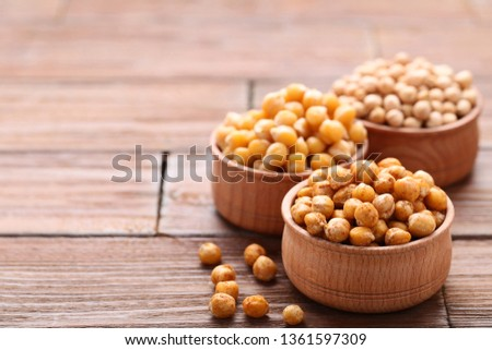 Roasted and dry chickpeas in bowls on brown wooden table #1361597309