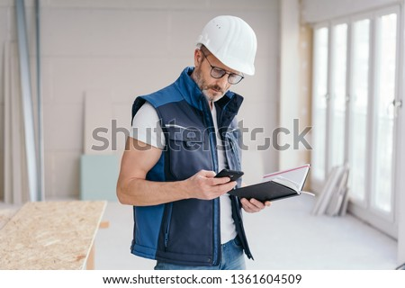 Builder checking a message on his mobile phone or making a call as he stands holding a journal on site in a new build house #1361604509