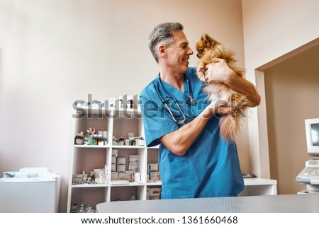 My best part of work! Middle aged positive vet in work uniform talking with small ginger dog while standing at veterinary clinic #1361660468
