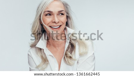 Elegant mid adult woman against white background. Stylish mature woman in white casuals looking away and smiling. #1361662445
