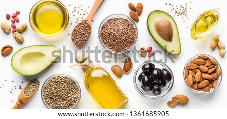 Avocado, almonds, hemp seeds, linseeds, olives and oils over white background, top view. Alternative oils concept #1361685905