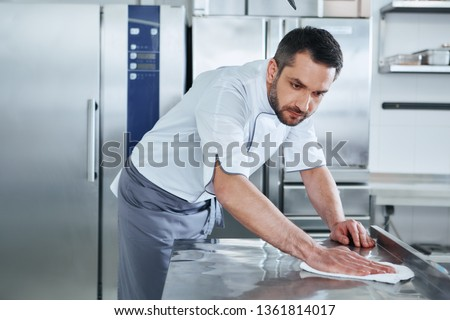 When preparing foods keep it clean, a dirty area should not be seen. Young male professional cook cleaning in commercial kitchen #1361814017