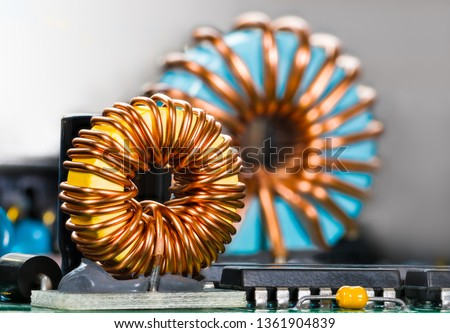Inductors detail. Copper wire winding. Magnetic ferrite core. Inverter. Beautiful colored coils in dismantled electric power supply unit. Colorful electronic parts. Chips, capacitor. Selective focus. #1361904839