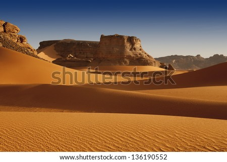 The removed rocks the remains of ancient volcanoes in the middle of desert. Dense sand with edge structure.  The Libyan desert - a fantastic place for travelers and photographers. #136190552