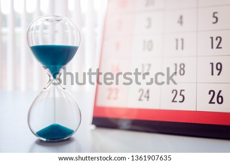 Hour glass and calendar concept for time slipping away for important appointment date, schedule and deadline #1361907635