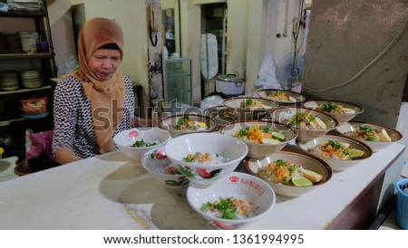 MADIUN - 18 JUNE 2018: An old woman is serving traditional food namely Soto in a famous food stall, Dawet Suronatan. #1361994995