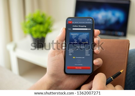man hands holding phone with online shopping on the screen in the house in room #1362007271