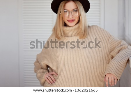 Stylish and beautiful young blonde in black felt hat and beige oversize sweater. Young woman with glasses, portrait #1362021665