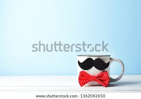 Coffee Mug with Mustache and Red Bow Tie over Blue Background, Happy Father's Day Concept #1362042650