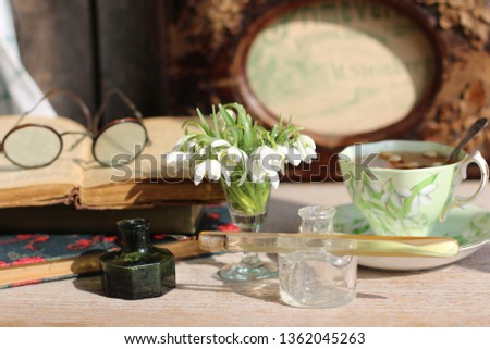 Spring composition with fresh first flowers in glass, antique pince-nez, old books, porcelain tea cup, weathered  frame background, vintage style #1362045263