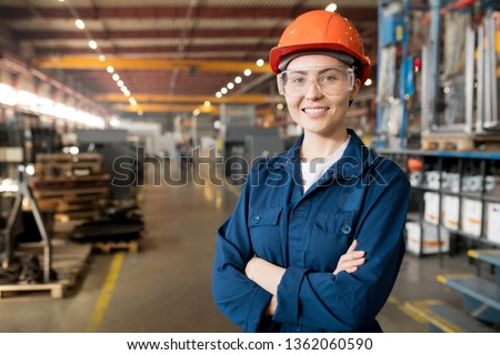 Young smiling female technician in blue uniform, protective eyeglasses and helmet working in modern factory #1362060590