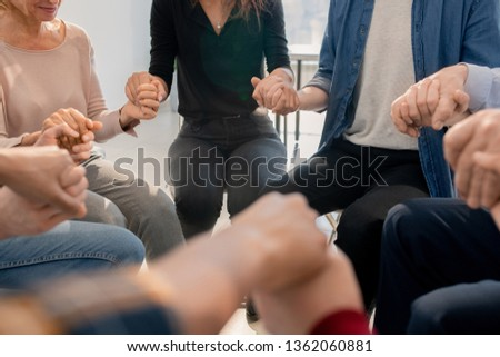 Group of troubled people holding by hands while sitting in circle during psychotherapy session #1362060881