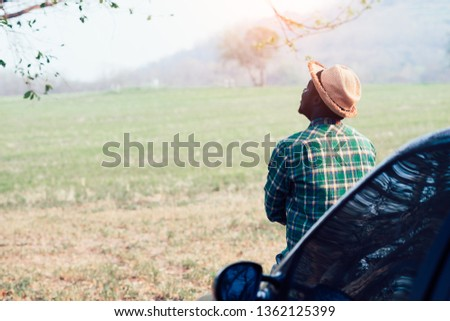 African man traveler hipster looking and sitting on the car #1362125399